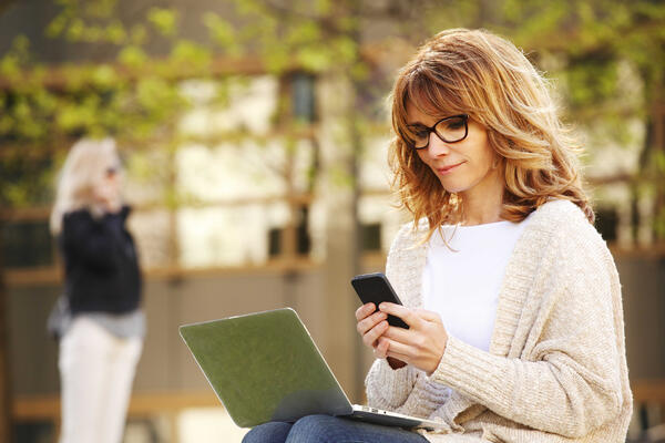 Women looking down at her smartphone and laptop